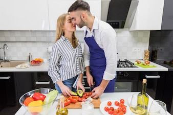 Couple cutting vegetables on board and kissing