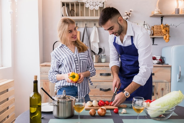 Couple cutting vegetables for salad on wooden board