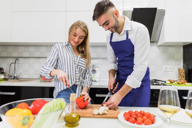 Couple cutting vegetables on wooden board