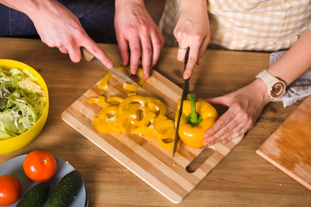 Couple cutting yellow pepper for salad