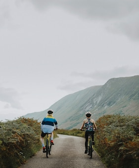 Couple cycling down a road in the scottish highlands