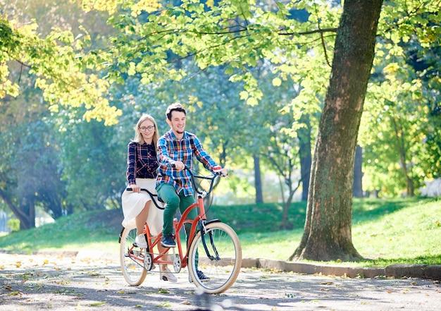 Пара, езда на велосипеде вместе на тандемном велосипеде