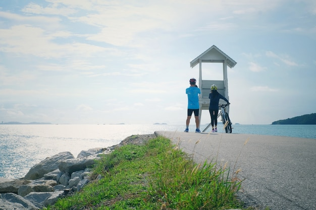 Couple cycling with seascape view of lifeguard tower at khao laem ya national park