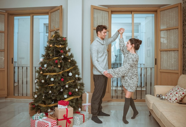Couple dancing holding hands near christmas tree