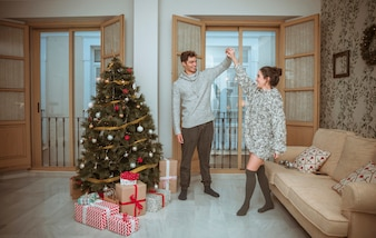Couple dancing in living room decorated for Christmas