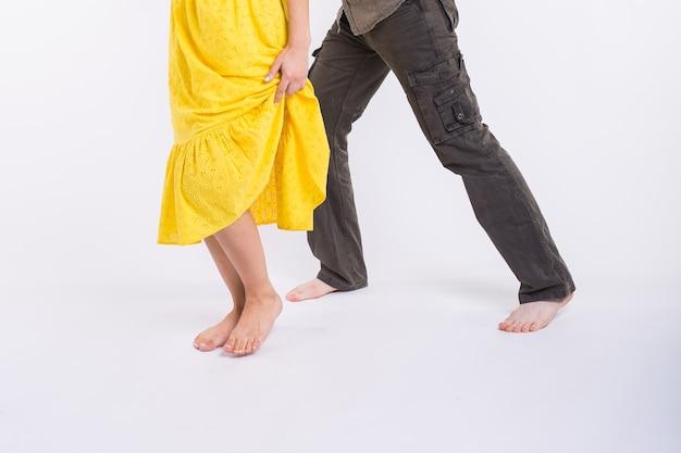 라틴 음악을 춤추는 커플. 바차타, 메렝게, 살사, 키좀바. 화이트 룸에 다리 우아함 포즈의 클로즈업.