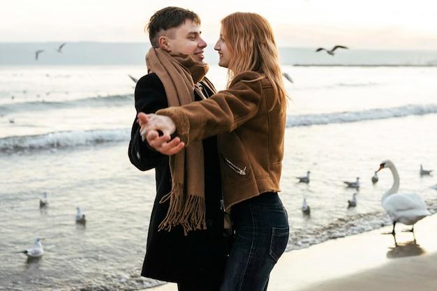 Пара танцует на пляже зимой