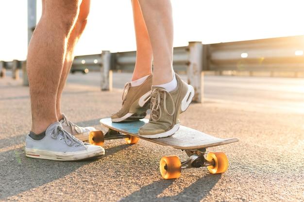 カップルのデート。日没時に通りで彼女のボーイフレンドの横にあるロングボードに立っている女の子。