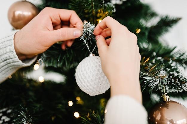 Пара украшает елку шаром мужчина и женщина украшают елку в помещении