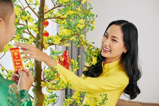 Couple decorating apricot tree