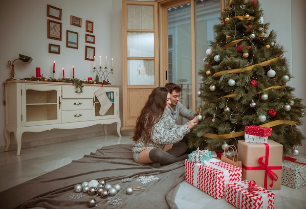 Couple decorating christmas tree sitting on floor