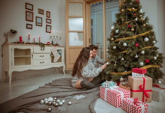 Couple decorating Christmas tree sitting on floor