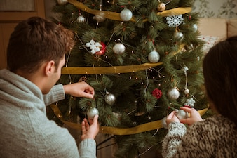 Couple decorating Christmas tree with silver balls