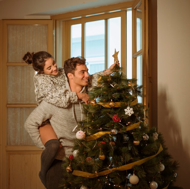 Couple decorating christmas tree with star