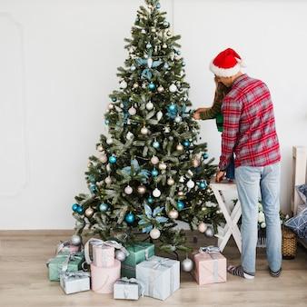 Coppie che decorano l'albero di natale