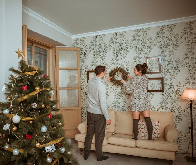 Couple decorating room for christmas