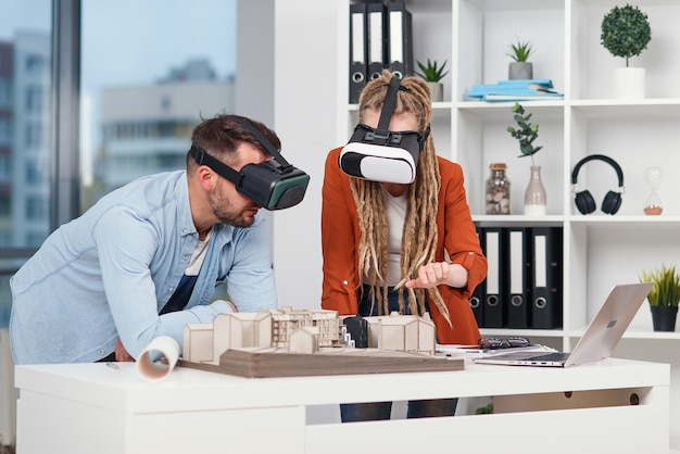 Couple of designers or engineers analyse mock-up of future residential area using ar goggles in architectural bureau.
