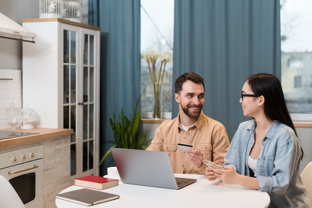 Couple at desk holding smartphone and credit card