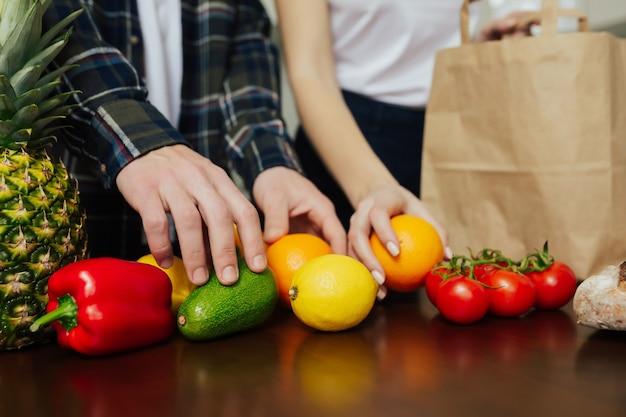 Пара разбирает покупки после покупок на кухне дома