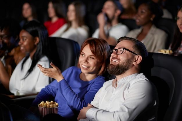 Пара обсуждает фильм в кинотеатре.