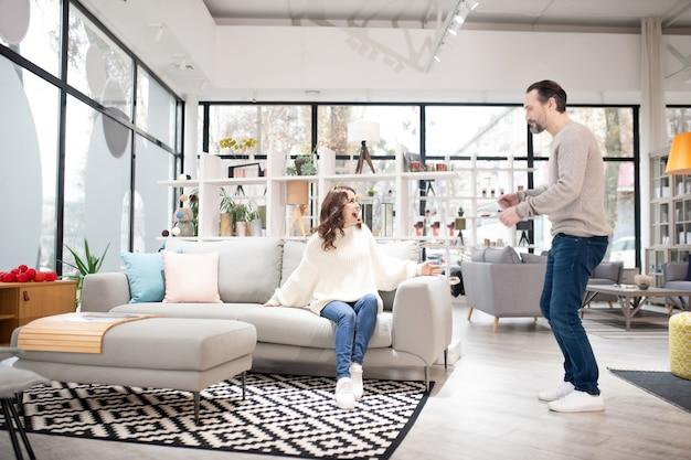 Пара обсуждает модели мебели в современном мебельном магазине