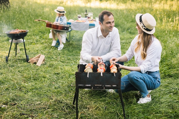 Пара делает барбекю на природе