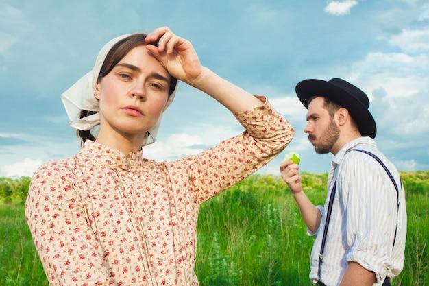 牧草地でピクニックをしているカップル