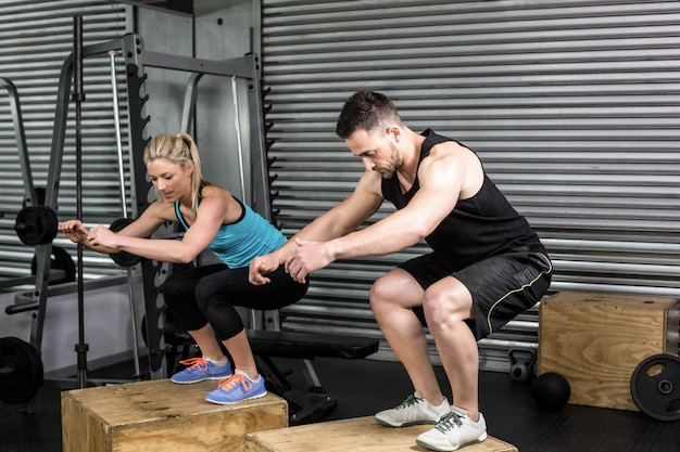 Couple doing box jumps in gym at gym