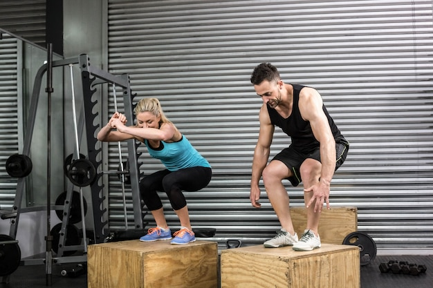 Couple doing box jumps in gym