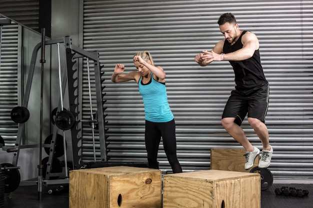 Crossfitジムでジムでボックスをしているカップルのジャンプ