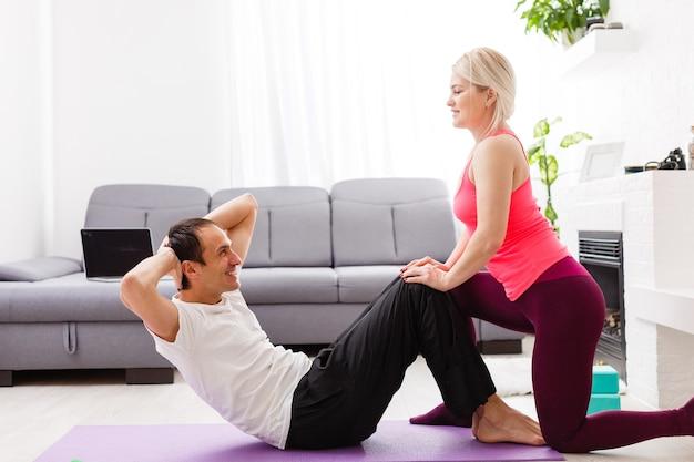 집에서 운동을 하는 커플. 요가 개념입니다.