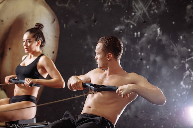 Couple doing exercises with rowing machine