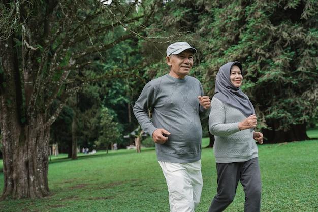 Пара делает упражнения, бегая в саду