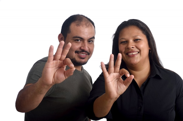 Couple doing the ok sign on white