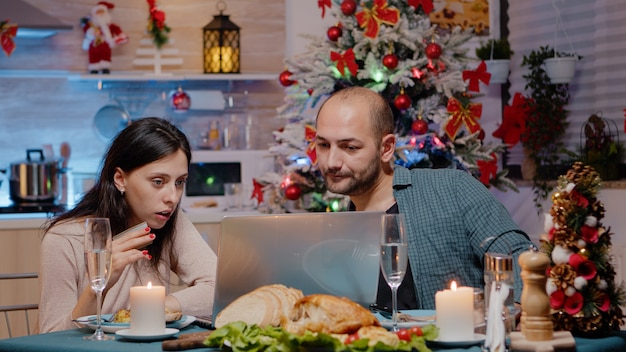 Couple doing online shopping on laptop with credit card