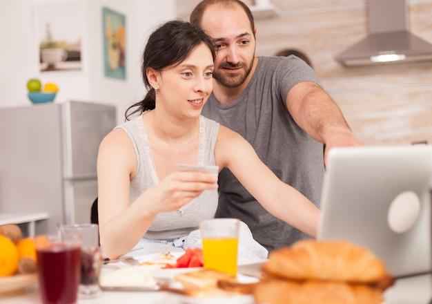 아침 식사 중에 노트북으로 온라인 쇼핑을 하는 커플. 정보 입력, 전자 상거래 기술을 사용하는 고객 웹에서 물건 구매, 코스머리즘 뱅킹 및 주문