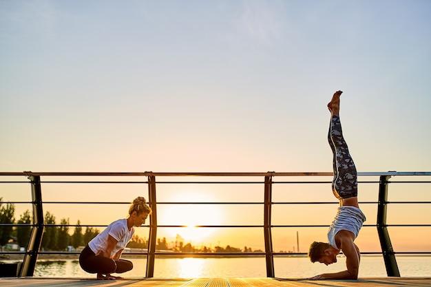 日の出で自然の屋外の朝の運動で一緒にヨガの練習をしているカップル