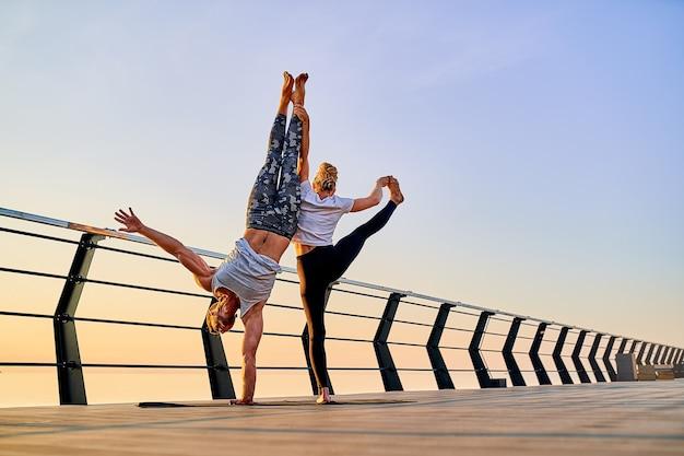 일출 때 야외에서 자연에서 함께 요가 연습을 하는 커플