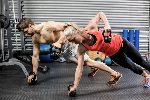 Couple doing push up with dumbbells at crossfit gym