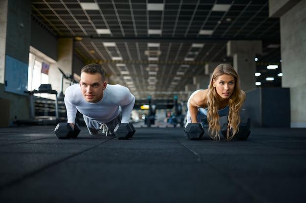 체육관에서 아령으로 팔굽혀펴기를 하는 커플