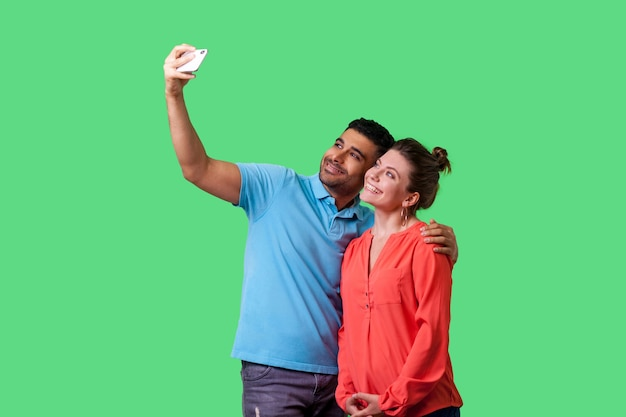 Couple doing selfie. portrait of positive young man and woman in casual wear standing, taking pictures together using cellphone, happy memories. isolated on green background, indoor studio shot