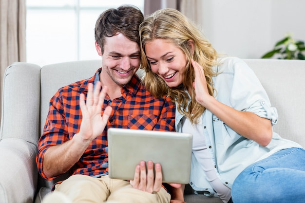 Couple doing video chat on a tablet computer in the living room
