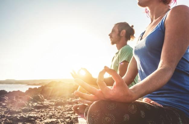 自然の日の出で屋外ヨガをやっているカップル-女と男の朝の時間で一緒に瞑想-健康的なライフスタイルと前向きな心のためのフィットネス運動の概念-女性の左手に焦点を当てる
