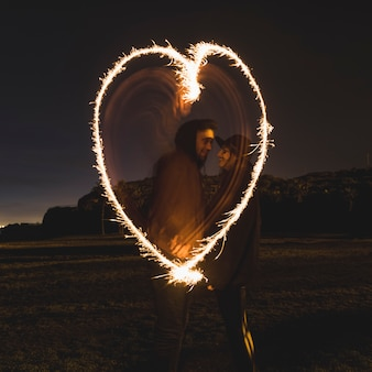Couple drawing heart from sparklers in dark street