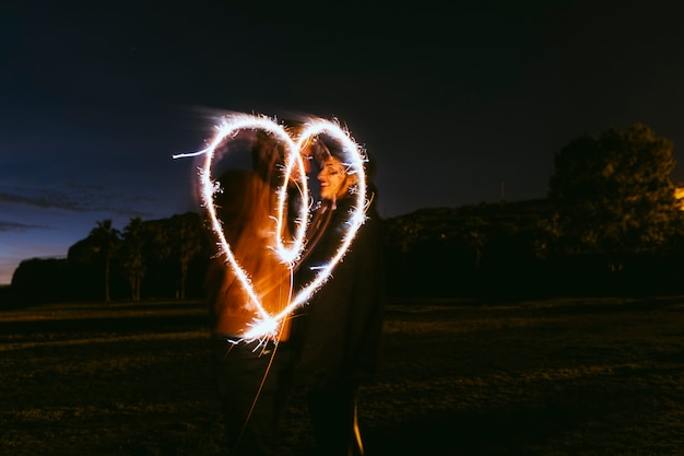 Couple drawing heart from sparklers in street