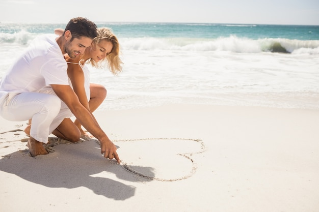 Couple drawing heart on sand