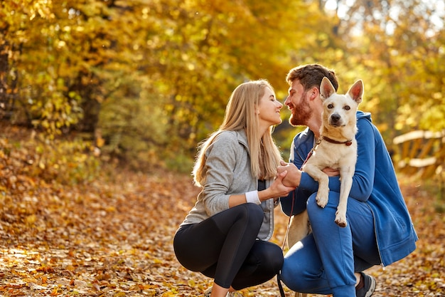 Couple dressed casual hugging and taking a walk in nature with their lovely nice dog , autumn season