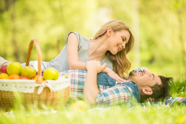 Couple dressed casual lying on the lawn in summer park.