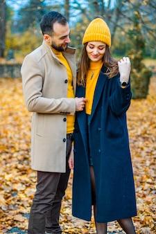 秋の公園で黄色いタートルネックと黄色い帽子に身を包んだカップル