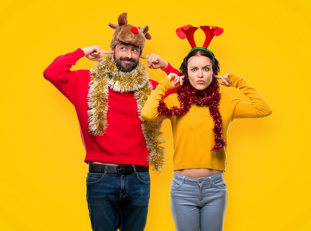 Couple dressed up for the christmas holidays covering ears with hands on yellow background